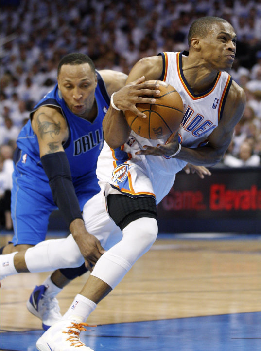 Oklahoma City Thunder guard Russell Westbrook, right, is fouled by Dallas Mavericks forward Shawn Marion, left, as he drives to the basket in the second quarter of Game 2 in the first round of the NBA