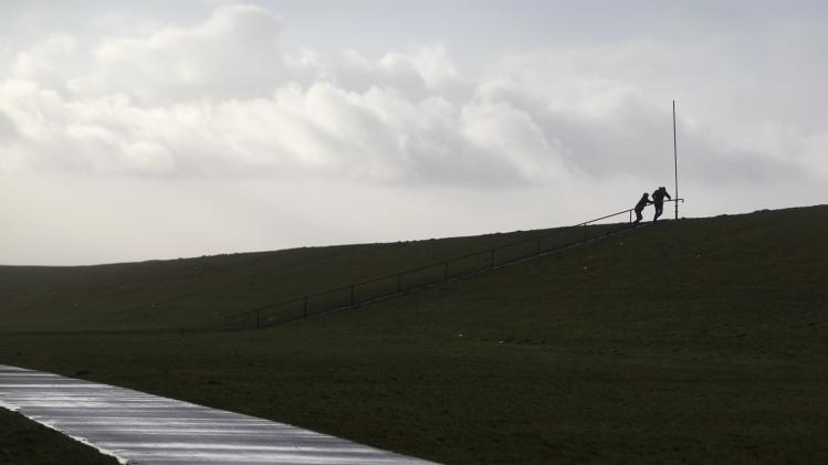 A couple walks on the North Sea dike near the town of Campen