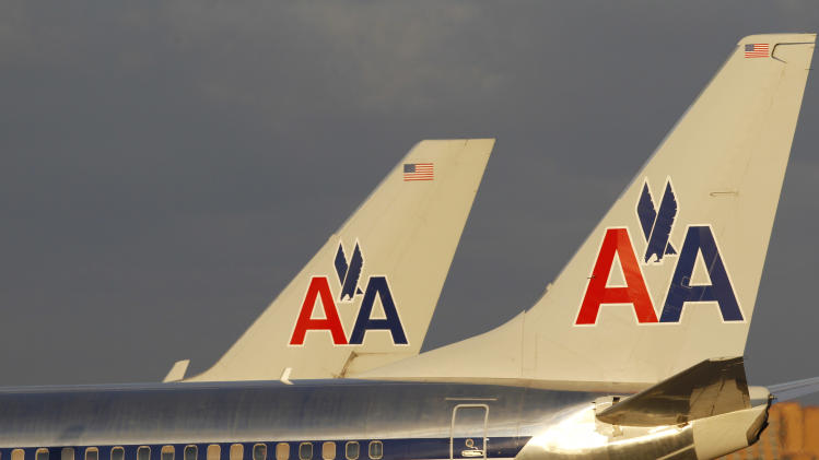 FILE - In this Thursday, Oct. 11, 2012, file photo, the tail sections of two American Airlines passenger jets are shown as they taxi at Miami International Airport in Miami. After years of losses, American Airlines is making money by boosting revenue and cutting labor costs. Parent company AMR Corp. said Thursday, Oct. 17, 2013, that it earned $289 million, or 76 cents per share, in the third quarter. That's a turnaround from a loss of $238 million, or 71 cents per share, a year earlier. (AP Photo/Wilfredo Lee, File)