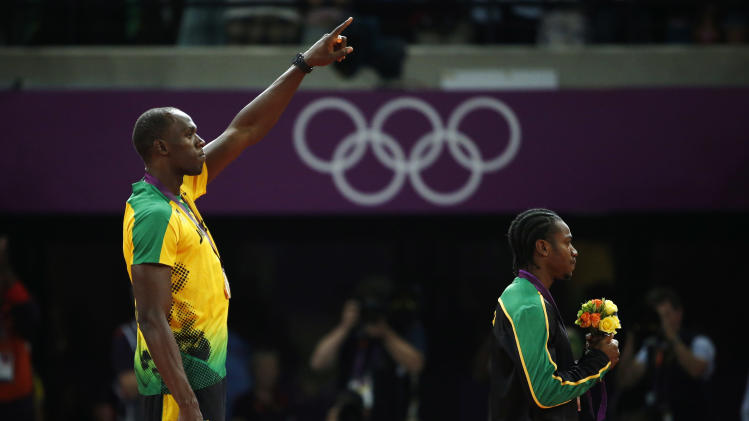 Jamaica's Usain Bolt, left, gestures as he stands on the podium after receiving his gold medal for the men's 200-meter, alongside silver medallist Jamaica's Yohan Blake, right, during the athletics in the Olympic Stadium at the 2012 Summer Olympics, London, Thursday, Aug. 9, 2012. (AP Photo/Matt Dunham)