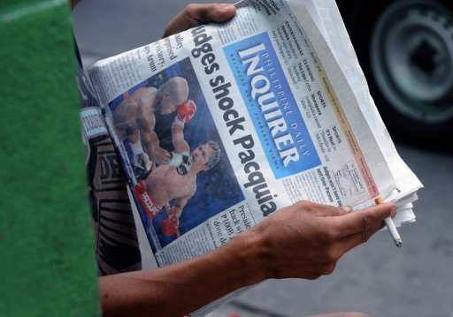 A man reads a newspaper showing Philippine boxing superstar Manny Pacquiao's title bout in Manila
