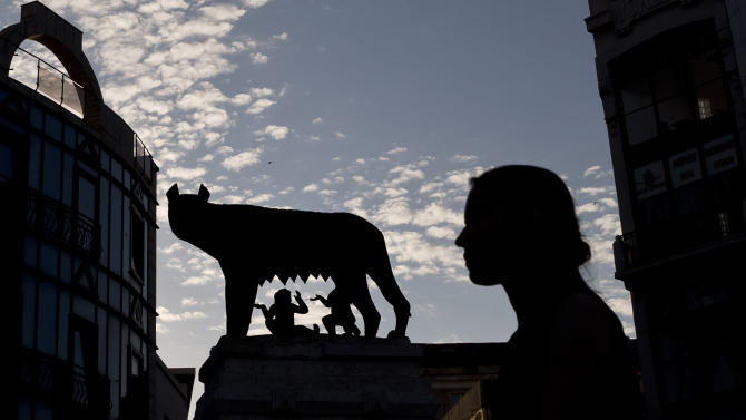 The statue of the she wolf feeding the mythical founders of the city of Rome, the twins Romulus and Remus, a 1906 gift from Rome to the Romanian capital, is silhouetted against the sunset sky downtown Bucharest, Romania, Tuesday, Sept. 16, 2014. Romania's education minister Remus Pricopie grabbed headlines and the latin origin proud country's wide attention after mistakenly stating during a television show that the twins were fed by a fox instead of a she wolf. (AP Photo/Vadim Ghirda)