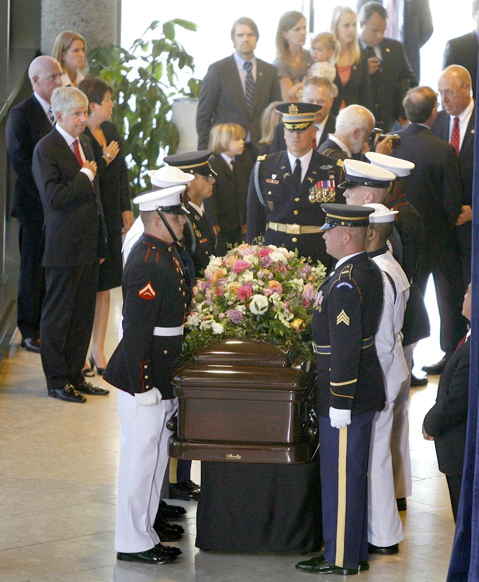 Michigan Gov. Rick Snyder, and his wife Sue, left, watch as the casket of former first lady Betty Ford is brought in by the military honor guard to the Gerald R. Ford Presidential Museum for the arrival ceremony Wednesday, July 13, 2011, in Grand Rapids, Mich. (AP Photo/The Grand Rapids Press, Rex Larsen, Pool)