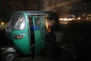 An auto rickshaw burns after being set on fire along a street in Dhaka