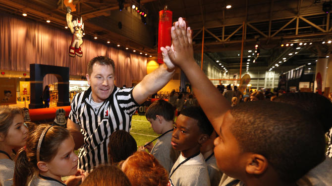 A Quaker referee high-fives a New Orleans kid at the Quaker's NFL Experience in New Orleans on Wednesday, Jan. 30, 2013. (Jonathan Bachman / AP Images for Quaker Oats)