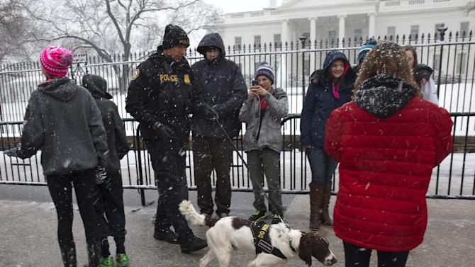 A Secret Service K-9 unit patrols between tourists visiting the White House under falling snow, Thursday, March 5, 2015, in Washington. The U.S. federal government said its offices in the Washington area will be closed Thursday because of a new round of winter weather expected in the region. The Office of Personnel Management said non-emergency personnel in and around Washington were granted excused absences for the day. Emergency employees and telework-ready employees were expected to work. (AP Photo/Jacquelyn Martin)