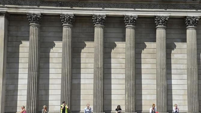 Workers relax during the lunch hour outside the Bank of England in the City of London