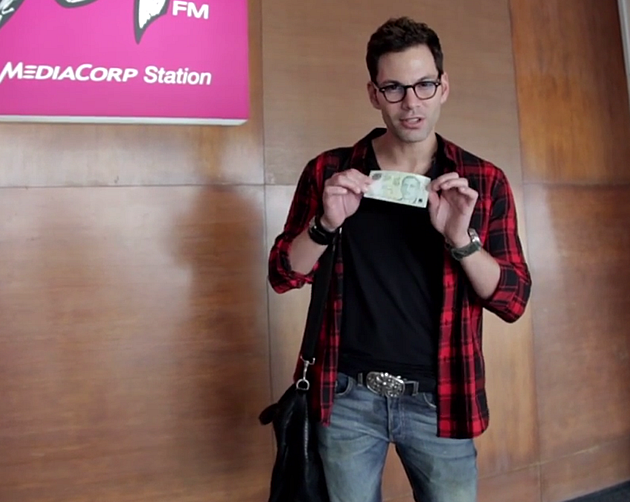 987FM deejay Bobby Tonelli poses with a $5 note, which he used in a day-long challenge. (Video screengrab)