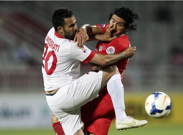 Sebastian Soria (R) of Qatar's Lekhwiya fights for the ball with Mohammed Nosrati of Iran's Tractor Sazi FC during their AFC Champions League soccer match in Doha