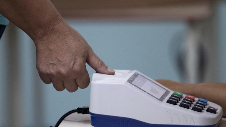 A voter uses a fingerprint scanner during elections in Caracas, Venezuela, Sunday, Dec. 16, 2012. Venezuelans are choosing governors and state lawmakers in elections that have become a key test of whether President Hugo Chavez's movement can endure if the leader leaves the political stage. (AP Photo/Ariana Cubillos)