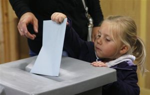 Little girl casts ballot for her mother in the Austrian general election at a polling station in Vienna