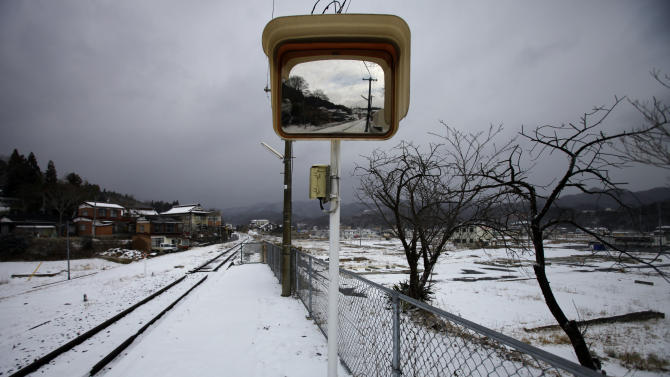 In this Sunday, Feb. 24, 2013 photo, a deserted train station is covered by snow in an area devastated by the March 11 2011 earthquake and tsunami, in Kesennuma, Miyagi Prefecture. Japan's progress in rebuilding from the tsunami that thundered over coastal sea walls, sweeping entire communities away, is mainly measured in barren foundations and empty spaces. Clearing of forests on higher ground due to be leveled to make space for relocating survivors has barely begun. Japan will next week observes two years from the March 11, 2011 disasters which devastated in the northeastern Pacific coast of the country. (AP Photo/Junji Kurokawa)