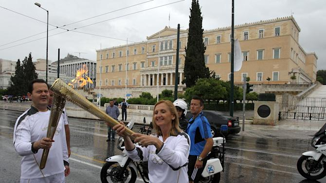 An unidentified torchbearer, left, passes the flame to Rena Sotiriadou during the Olympic flame relay for the 2012 London Olympics, in front of the Greek Parliament in Athens, Thursday, May 17, 2012. The Olympic flame will travel to London, where the Summer Games will take place from July 27-Aug. 12. (AP Photo/Thanassis Stavrakis)