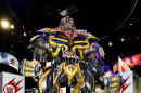 A young fan poses with a huge Transformers display during preview night at the 2014 Comic-Con International Convention held Wednesday, July 23, 2014 in San Diego. (Photo by Denis Poroy/Invision/AP)