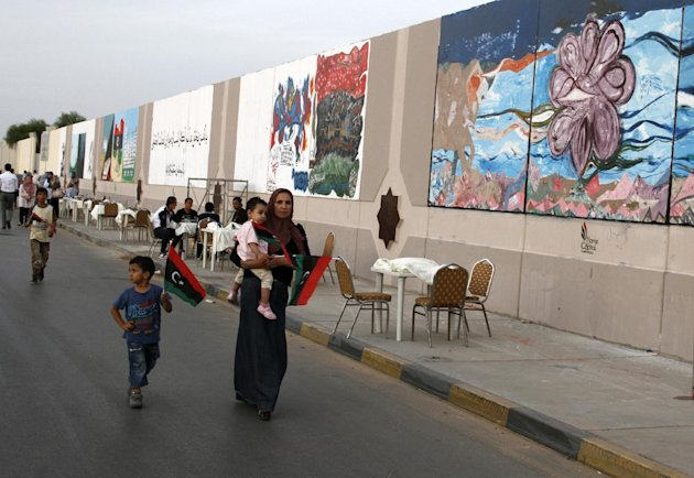 In this Tuesday, Oct. 23, 2012 photo, a Libyan family in Tripoli walk by a mural exhibition celebrating one year since the fall of dictator Muammar Gadhafi in Tripoli, Libya. One year on, the country is still trying to overcome the legacy of one of the most erratic leaders of modern times as well as a brutal eight month struggle that left the country awash in weapons, militias and very few viable institutions of the state. (AP/Paul Schemm)