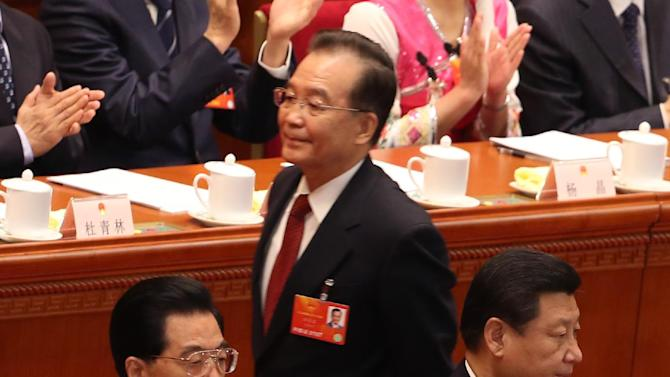 Chinese Premier Wen Jiabao, top walks past Chinese Communist Party General Secretary Xi Jinping, right, and Chinese President Hu Jintao, during the opening session of the National People's Congress in Beijing's Great Hall of the People, China, Tuesday, March 5, 2013. China's government promised its people Tuesday deficit-fueled spending to fight deep-seated corruption, improve the despoiled environment and address other quality-of-life issues demanded by an increasingly vocal public looking for change.  (AP Photo/Kin Cheung)