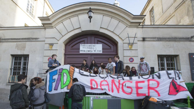 "Students set up barricades and display a banner reading ""Education in danger"" outside their highschool to protest against immigration policy, in Paris, Thursday, Oct.17, 2013. Kosovan girl Leonarda Dibrani was finishing up a field trip when French police showed up at the bus, detaining the 15-year-old schoolgirl in front of her classmates before authorities expelled her to Kosovo because her family's asylum application had been rejected. The incident earlier this month, but which was made public this week, has sparked outrage from immigrant groups and others who say police went too far in publicly shaming the teenager. (AP Photo/Jacques Brinon)"