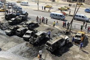 People stand at the site of a car bomb attack in Baghdad