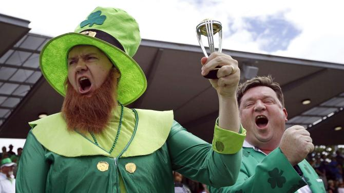 An Ireland supporter holds a replica World Cup trophy as he sings the national anthem before the start of the Cricket World Cup match between Ireland and South Africa in Canberra