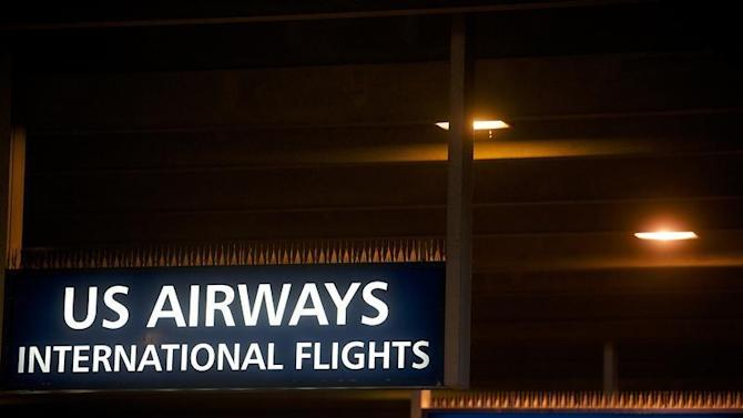 US Airways and American Airlines signs are pictured at Philadelphia International Airport