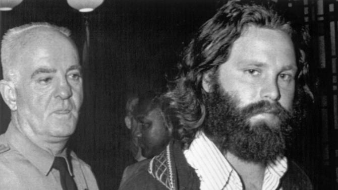 FILE - In this Oct. 30, 1970, file photo, singer Jim Morrison leaves a courtroom in Miami, Fla., in the custody of a police officer after he was sentenced to six months in jail and fined for $500 for using profanity in public and indecent exposure. A group of fans want his home to be a historical site and placed in a list of tourist attractions in the city of Albuquerque, N.M., KOAT-TV reports. Historian and fan Anthony Gomez says because Morrison spent important years in New Mexico's biggest city, his childhood home should be protected as a remembrance. (AP Photo/File)