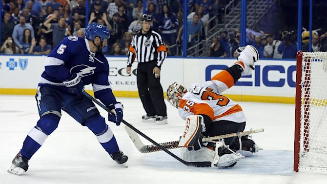 Jason Garrison of the Tampa Bay Lightning scores an overtime goal against the Philadelphia Flyers at the Amalie Arena in Tampa, Florida, on October 8, 2015
