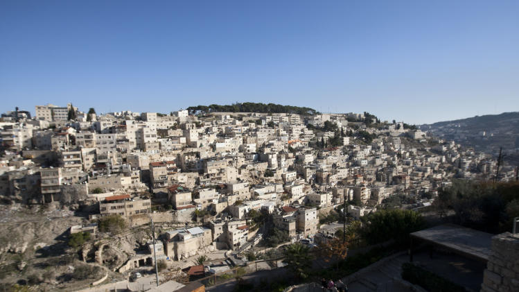 This photo taken on Dec. 1, 2011, shows a view of the excavation site known as the City of David, bottom, with the background of the Palestinian neighborhood of Silwan near Jerusalem's Old City.  Mysterious stone carvings made thousands of years ago and recently uncovered in the excavation of the city of David have archaeologists stumped. (AP Photo/Sebastian Scheiner)