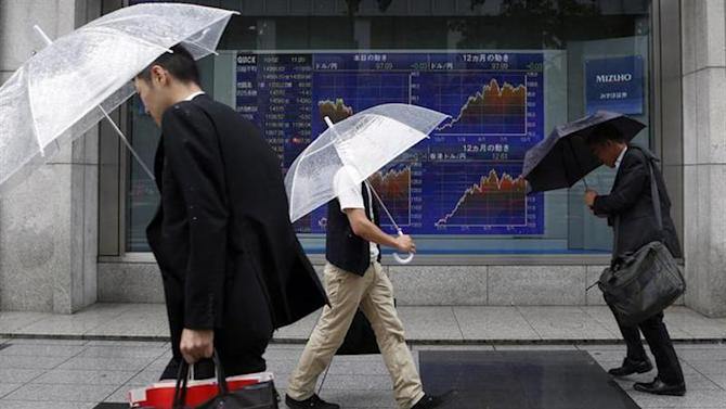Men walk against strong wind and rain in front of a stock quotation board outside a brokerage in Tokyo October 2, 2013. REUTERS/Toru Hanai