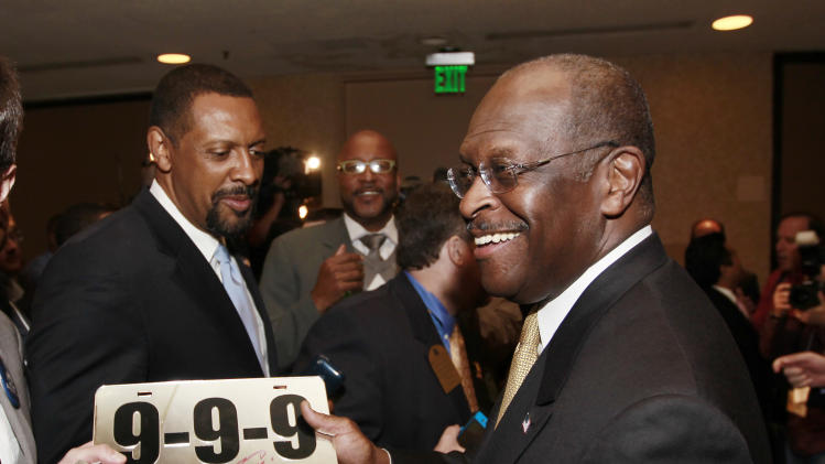 Republican presidential candidate Herman Cain signs a car tag, bearing 9-9-9, a reference to his tax reform plan, after speaking to the board of The Federation of Young Republicans Saturday, Nov. 12, 2011, in Atlanta.  (AP Photo/John Bazemore)