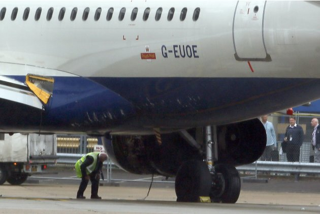 A worker looks at a British Airways passenger jet after it was towed off the runway following an emergency landing at Heathrow Airport west of London
