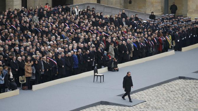 French President Francois Hollande leaves the podium to cross the courtyard during a ceremony to pay a national homage to the victims of the Paris attacks at Les Invalides monument in Paris
