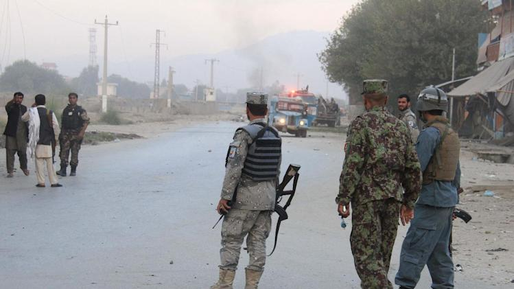 Afghan security forces inspect the site of a suicide attack in Jalalabad, east of Kabul, Afghanistan, Saturday, Aug. 30, 2014. A suicide bomber in a truck blew himself up at an intelligence headquarters in eastern Afghanistan on Saturday, setting off an intense firefight with security forces, officials said. (AP Photo)