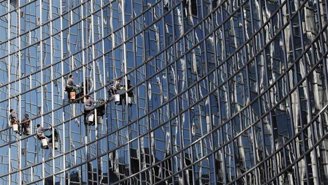 Workers clean a glass wall reflecting other skyscrapers at a hotel in Beijing, October 24, 2013. REUTERS/Kim Kyung-Hoon