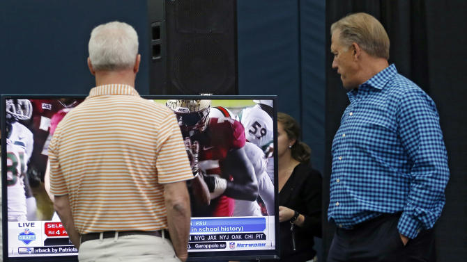 Denver Broncos head coach John Fox and vice president John Elway, right, keep up with the NFL draft on a television in the media center as second round draft pick Indiana wide receiver Cody Latimer speaks to the media at the NFL football teams headquarters in Englewood, Colo., on Saturday, May 10, 2014. (AP Photo/Ed Andrieski)