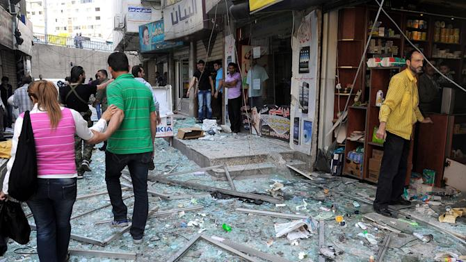In this photo released by the Syrian official news agency SANA, Syrians walk on shattered glass from damaged shops at the scene of a powerful explosion which occurred in the central district of Marjeh, Damascus, Syria, Tuesday April 30, 2013. A powerful explosion rocked Damascus on Tuesday, causing scores of casualties, a day after the country's prime minister narrowly escaped an assassination attempt in the heart of the heavily protected capital. (AP Photo/SANA)