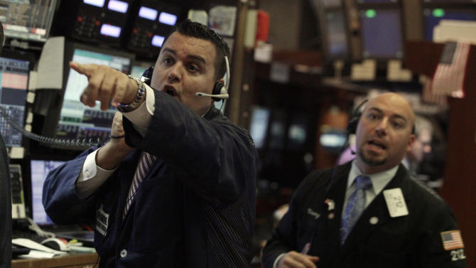 Trader Bobby Finnerty, left, calls to a colleague on the floor of the New York Stock Exchange Wednesday, Aug. 1, 2012. Stocks are mostly higher in morning trading. (AP Photo/Richard Drew)