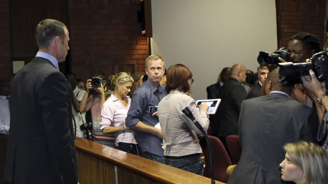 Olympic athlete Oscar Pistorius, left,  stands as the judges leaves the court, during his bail application at the magistrate court, in Pretoria, South Africa, Tuesday, Feb. 19, 2013.  Pistorius fired into the door of a small bathroom where his girlfriend was cowering after a shouting match on Valentine's Day, hitting her three times, a South African prosecutor said Tuesday as he charged the sports icon with premeditated murder. The magistrate ruled that Pistorius faces the harshest bail requirements available in South African law. He did not elaborate before a break was called in the session. (AP Photo/Themba Hadebe)