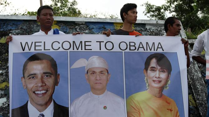 People holding a poster with portraits of U.S. President Barack Obama, left, Myanmar President Thein Sein, center, and Myanmar opposition leader and Nobel laureate Aung San Suu Kyi as they wait to welcome the arrival of U.S. President Barack Obama at Yangon International Airport Monday, Nov. 19, 2012, in Yangon, Myanmar. (AP Photo/Khin Maung Win)