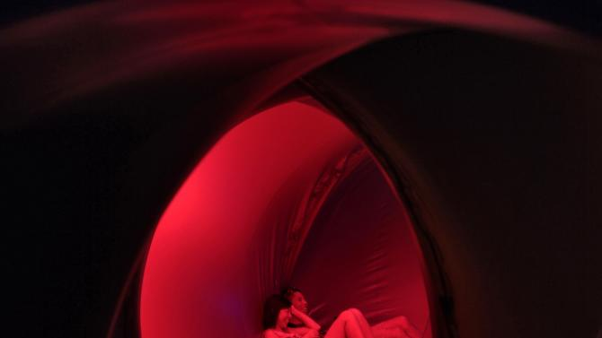Sandy Chang and Orson Cheong relax on the floor inside Exxopolis, an inflatable walk-in luminarium at Grand Park in Los Angeles, California