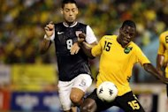 Clint Dempsey (L) of the United States battles for the ball with Je-Vaughn Watson of Jamaica during the United States and Jamaica World Cup Qualifier at National Stadium on September 7, in Kingston, Jamaica