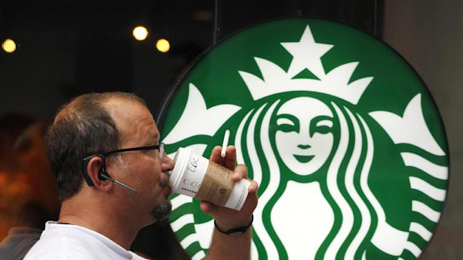 FILE - In this July 11, 2013 file photo, a man drinks a Starbucks coffee in New York. Starbucks reports quarterly financial results on Thursday, July 24, 2014. (AP Photo/Mark Lennihan, File)