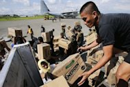 <p>Philippine Army personnel unload relief goods at an airport in Mindanao on December 15, 2012. Typhoon Bopha killed 1,020 people, mostly on Mindanao island, where floods and landslides caused major damage on December 4, civil defence chief Benito Ramos said.</p>