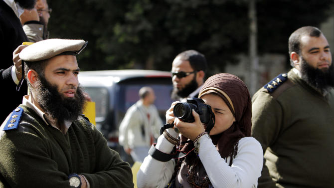 FILE - In this Monday, March 4, 2013, file photo, a journalist take pictures of Egyptian Salafi Muslims, unseen, during a protest in support of bearded police officers who were prevented from carrying out their work in the interior ministry, in front of the Shura Council, the upper house of Parliament, in Cairo, Egypt. Amid Egypt's multiple woes under an Islamist-dominated administration, religion is not the political selling point it once was among Egyptians, one factor fueling planned weekend protests calling for Morsi's fall. (AP Photo/Amr Nabil, File)