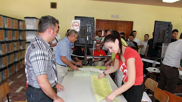 Election officials count votes in Tirana, Monday, June 24, 2013 after Albania's national elections, which were marred by gunfire at a polling station leaving one man dead and two others wounded. Initial returns indicated a narrow lead for the opposition Socialist Party-led coalition of Edi Rama, who is running against Prime Minister Sali Berisha of the Democratic party. Both men claimed victory after polls closed Sunday evening. (AP Photo/Hektor Pustina)