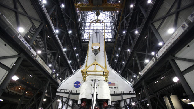 Space shuttle Atlantis is lifted to a vertical position to be attached to its external fuel tank and two solid rocket boosters in the Vehicle Assembly Building at the Kennedy Space Center in Cape Canaveral, Fla., Wednesday, May 18, 2011. Atlantis is targeted for a mid July launch.(AP Photo/John Raoux)
