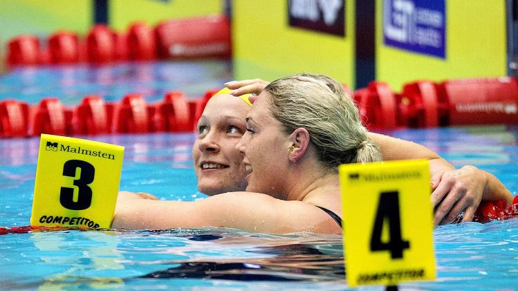 First placed Sjoestroem of Sweden celebrates with second placed Jeanette Ottesen of Denmark after their women's 50m Butterfly final during the LEN European Short Course Swimming Championship in Herning