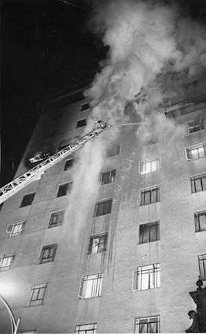 FILE - In a Dec. 20, 1970 file photo Tucson, Ariz., firefighters apply a steady stream of water during the Pioneer International Hotel fire , that resulted in 29 deaths.      Louis Cuen Taylor who has spent more than four decades in prison for the hotel fire is expected to be released Tuesday, April 2, 2013, as part of a deal with prosecutors.  (AP Photo/The Tucson Citizen, file )