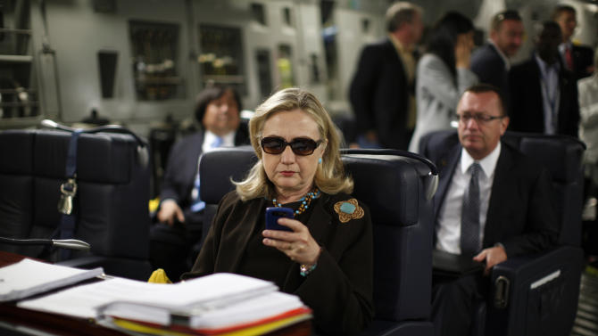 "FILE - In this Oct. 18, 2011, file photo, then-Secretary of State Hillary Rodham Clinton works from a desk inside a C-17 military plane upon her departure from Malta, in the Mediterranean Sea, bound for Tripoli, Libya. Clinton has joined Twitter, describing herself as a ""pantsuit aficionado"" and a ""hair icon."" The potential 2016 presidential candidate's profile page shows the infamous photo of the stern-looking Clinton wearing dark sunglasses and reading her Blackberry. (AP Photo / Kevin Lamarque, Pool, File)"