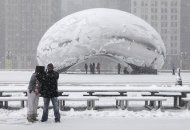 <p>               Onlookers take pictures in front of Cloud Gate, a public sculpture by Indian-born British artist Anish Kapoor, as they walk around the Millennium Park as a snow storm passes through the region Tuesday, March 5, 2013, in Chicago. Chicago was hit Tuesday by a storm expected to dump as much as 10 inches of snow in the area before the end of the day — the most since the 2011 blizzard and its more than 20 inches of snow. (AP Photo/Kiichiro Sato)