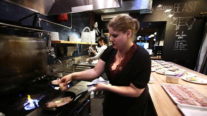 FILE - In this Sept. 27, 2013 file photo,Sous Chef Maya Lovelace prepares quail at Beast Restaurant in Portland, Ore. The Institute for Supply Management issues its U.S. non-manufacturing (service-sector) index for September on Thursday, Oct. 3, 2013. (AP Photo/Don Ryan, File)
